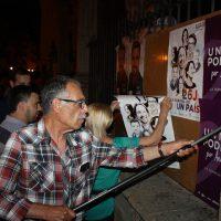 Un miembro de Unidos Podemos pegando carteles.