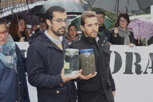 El alcalde de Arriate y el portavoz de IU muestran el agua antes y después de pasar por el pueblo.