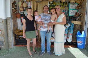 La familia que regenta el negocio en la puerta de la tienda.