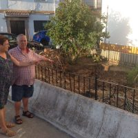 """Mari y Domingo, dos de los vecinos, muestran el jardín en el que se encontraban las palmeras """"robadas""""."""