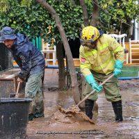 Un vecino y un bombero forestal del Infoca retiran lodo en las calles de Jimera de Líbar.